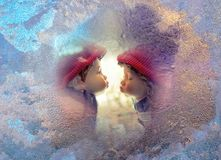 Love concept at the First kiss. Boy and girl kissing on frozen window frame in winter day. Love concept at First kiss - holidays postcard for Valentines Day Royalty Free Stock Photo