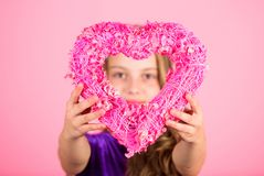 Love concept. Girl cute child show heart shaped decor. Symbol of love. Kid adorable girl with long hair happy face show. Heart to you. Look in heart part royalty free stock photography