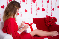 Love concept - gorgeous woman in red dress opening gift box in d Stock Photos