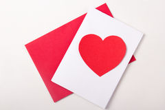 Love concept - handmade card with red paper heart over white Stock Photography