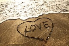 Love concept handwritten on sand Royalty Free Stock Image