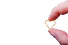 Love Concept. Heart shaped pasta held in two fingers. Isolated Royalty Free Stock Photography