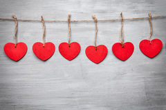 Love concept. Hearts hanging on a string. Shot on grey background royalty free stock photos