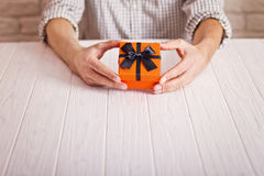 Love concept. Man holding orange gift with black ribbon in hands. Women`s day. St. Valenine`s day Royalty Free Stock Photography