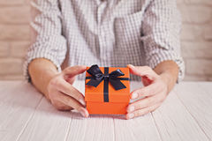 Love concept. Man holding orange gift with black ribbon in hands. Women`s day. St. Valenine`s day Stock Image