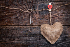 Love concept. Old key and a heart on wooden background Stock Image