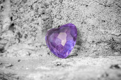 Love concept with purple heart on stoned wall. Background Royalty Free Stock Photo