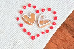 Ripe red berries in a heart shape and cakes. Love concept with red berries out in the form of heart  and  cookies in the form of heart  on a white tied Royalty Free Stock Photos