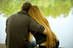 Love concept: two lovers hugging. Lovers hugging and sitting on lakeside Royalty Free Stock Images