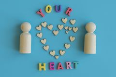 Love concept. Two wooden figures and a heart on a blue background. Love concept Two wooden figures and a heart on a blue royalty free stock images