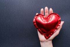 Valentine`s Day. The Hand of a girl holds a red heart on a dark background. Flat Lay top view closeup. stock images