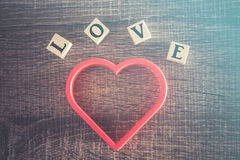Love concept. Valentines day background. With red heart and Love message written in wooden blocks Stock Photography
