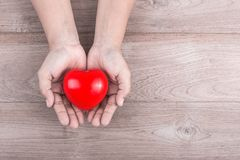 Love Concept : Woman hands holding red heart on brown wooden tab