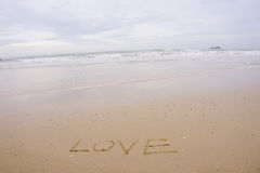 Love concept , written by hand in sand on a sea beach with soft wave. Stock Photo