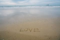 Love concept , written by hand in sand on a sea beach with soft wave. Stock Image