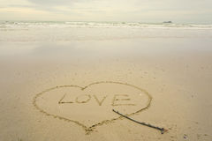 Love concept , written by hand in sand on a sea beach with soft wave. Royalty Free Stock Photo