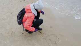 Love concept. Young attractive woman drawing a heart on the sand. Spring at Baltic sea. Love concept. Young attractive woman drawing a heart on the sand stock footage