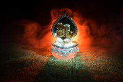 Love concepts of wedding teddy bear in silver heart gift box on table for valentines day and wedding. Dark smoky toned background. Selective focus Royalty Free Stock Photography