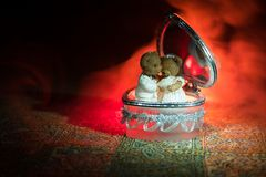 Love concepts of wedding teddy bear in silver heart gift box on table for valentines day and wedding. Dark smoky toned background. Selective focus Royalty Free Stock Images