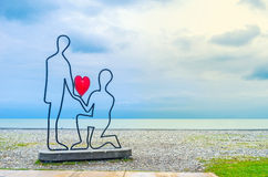 The love confession. BATUMI, GEORGIA - MAY 24, 2016: The sculpture of a couple, making the love confession on the beach, on May 24 in Batumi Stock Photos