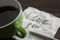 Love confession on napkin. Romantic message written on napkin and cup of coffee on wooden table Stock Photo