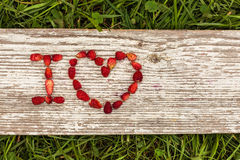 Love Confession. Strawberries are laid out in the letters on a background of green grass and board Stock Image