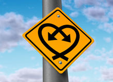 Love Connection. Love road sign with two curved arrows in the shape of a heart showing the crossing paths of lovers and couples in a dating or sex relationship Royalty Free Stock Image