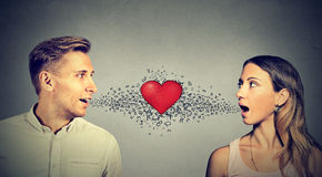 Love connection. Man woman talking to each other red heart in-between Royalty Free Stock Images