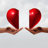 Love Connection. Romance and relationship couple trouble concept as two human hands holding a valentine day heart that is divided as a symbol for emotional Royalty Free Stock Image