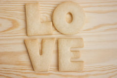 Love cookies. Word love spelled with home made cookies on a wooden table. Valentine's Day baking concept royalty free stock photo