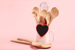 Love and Cooking concept; Wooden kitchen utensils on pink background. Stock Photo