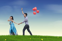 Love couple with balloon. Happy young couple in love with red heart balloon Royalty Free Stock Photography