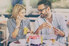 Love couple on breakfast break. Women using smartphone while having breakfast, filtered image royalty free stock image