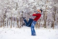 Love couple in bright clothes playing outdoors in winter. Snow park Royalty Free Stock Photos