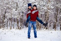 Love couple in bright clothes playing outdoors in winter. Snow park Royalty Free Stock Image