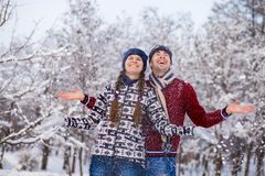 Love couple in bright clothes playing outdoors in winter. Snow park Royalty Free Stock Photo