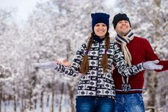 Love couple in bright clothes playing outdoors in winter. Snow park Stock Photos