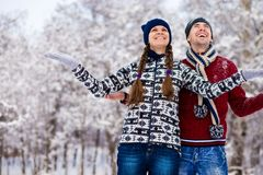 Love couple in bright clothes playing outdoors in winter. Snow park Stock Images