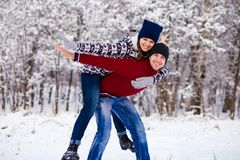 Love couple in bright clothes playing outdoors in winter. Snow park Stock Photography
