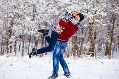 Love couple in bright clothes playing outdoors in winter. Snow park Royalty Free Stock Images