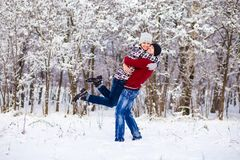 Love couple in bright clothes playing outdoors in winter. Snow park Royalty Free Stock Photography