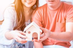 Love Couple buy a new home. Holding wooden house model royalty free stock images