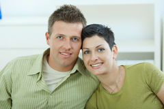 Love couple cuddling. Happy young love couple cuddling at home, smiling royalty free stock photo
