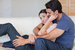 In love couple cuddling each other. In their living room stock photo