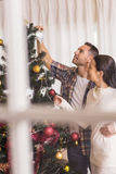 Love couple decorating the christmas tree together. At home in the living room Stock Photos