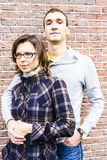 Love couple embracing looking happy against wall bac. Portrait of love couple embracing looking happy against wall background Stock Image