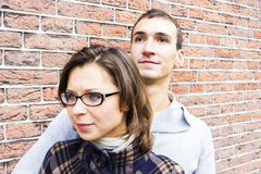Love couple embracing looking happy against wall bac. Portrait of love couple looking happy against wall background Royalty Free Stock Photo
