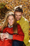 Love couple embracing and loving in season - autumn park, coloursfull leaves, pregnant woman, smiling healthy couple, sunny day Royalty Free Stock Photography