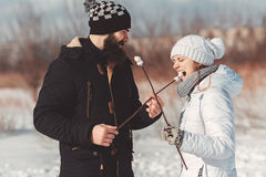 In love couple feeding each other a delicious fried marshmallow. Hungry couple in warm clothes standing in winter field. he feeds her marshmallow. Lovers laugh Royalty Free Stock Images