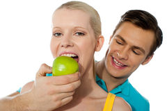 Love couple. Girlfriend eating an apple. Boyfriend making her partner eat an apple. Love couple Stock Images